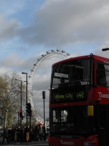 A doubledecker bus for tourists with the London Eye in the background.